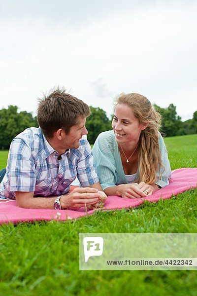 Mid adult couple lying on blanket and looking at each other