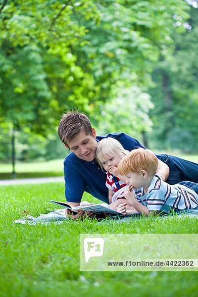 Father reading book to son and daughter in park