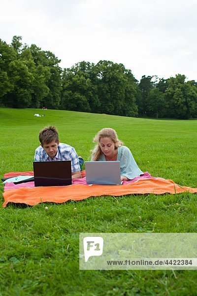 Mid adult couple lying on blanket and using laptops