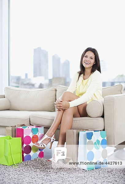 Smiling woman sitting in living room with shopping bags pe0074454