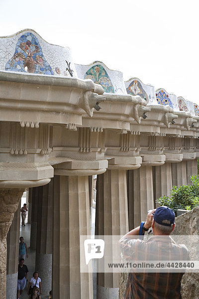 Tourist die Bilder am Parc Güell  die serpentine mehrfarbig Mosaik-Bank  Barcelona  Spanien.