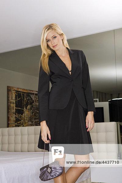 Elegante Frau steht in ihrem Schlafzimmer