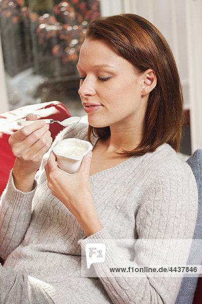 Junge Frau beim Joghurtessen