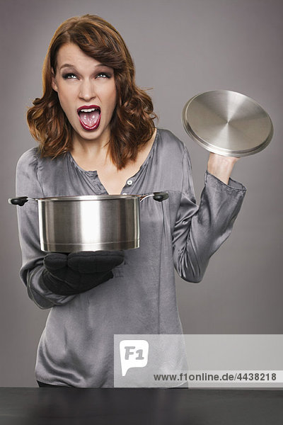 Young woman looking at content of stew pot