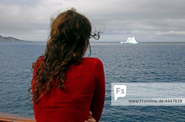 Woman on a cruise ship looking at an Iceberg in Arsuk Fjord along the southwest coast  Greenland