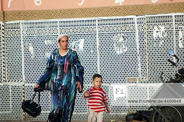 Marrakesh (Morocco): mother and child walking in Djemaa el Fna Square