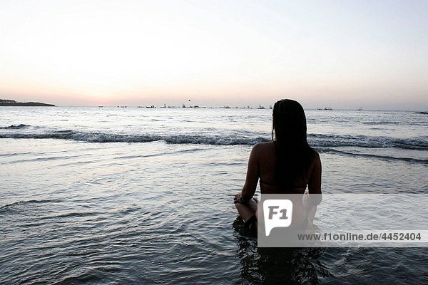 Woman sitting in the water after sunset. Tamarindo beach  Nicoya peninsula  Costa Rica