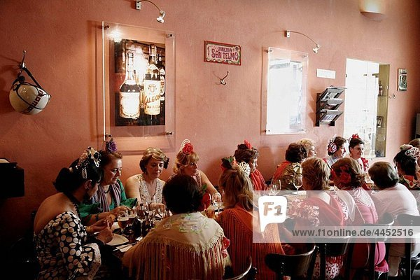 Women wearing traditional flamenco dress sitting at a restaurant during the April Fair  Seville  Spain.