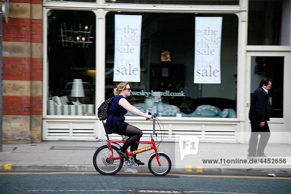 Woman ride a bicycle  Manchester  England  UK