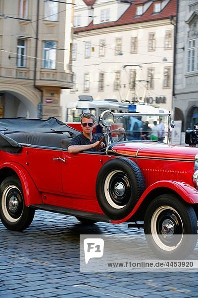 Young man drives an old Skoda car which is used for sightseeing  Prague  Czech Republic