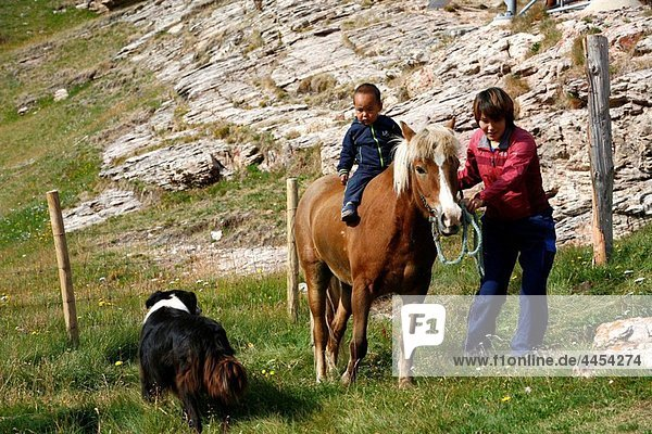 Woman riding a horse with her baby at Qassiarsuk  South Greenland