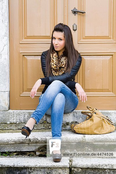 Sitting with legs crossed young woman