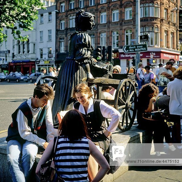 Young people sitting by Molly Malone statue  Grafton street  Dublin  Ireland
