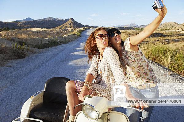 Frauen auf dem Motorrad beim Fotografieren