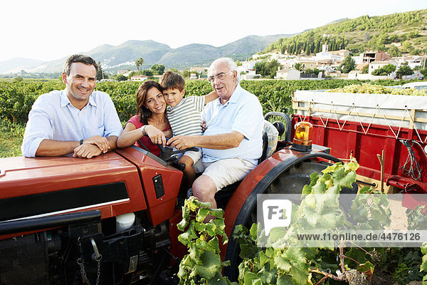 Generationsfamilie auf dem Traktor sitzend
