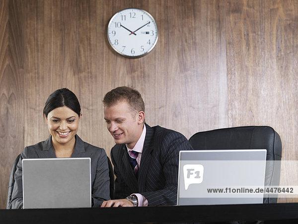 Geschäftsmann und Geschäftsfrau am Schreibtisch