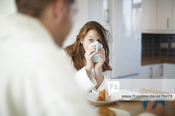 Mädchen trinkt Kaffee in der Küche