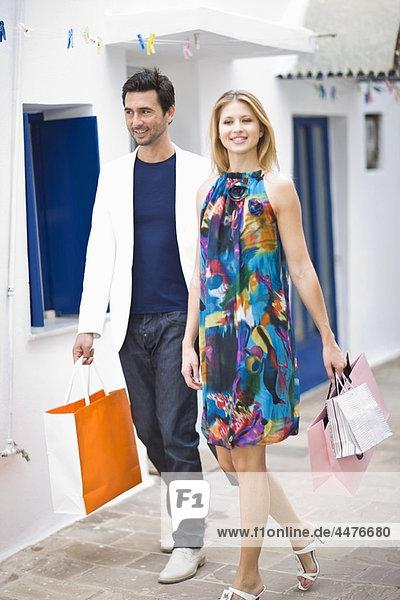Paar mit Einkaufstaschen zu Fuß