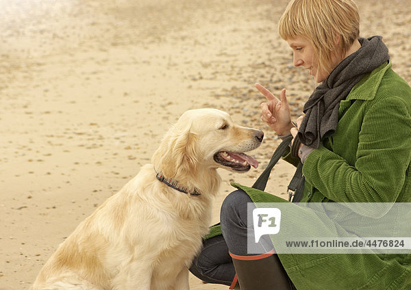 Frau Training Hund am Strand Herbst Herbst