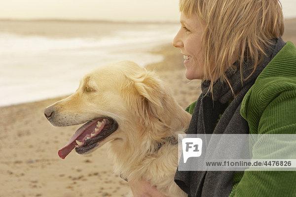 Frau und Hund am Strand