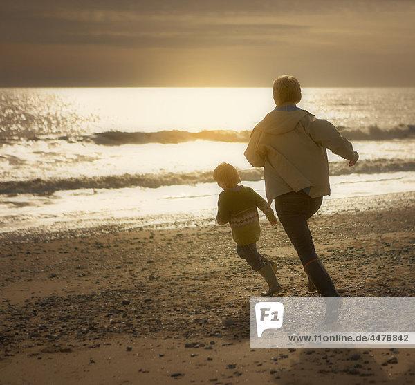 Eine Frau jagt einen kleinen Jungen am Strand. Herbst