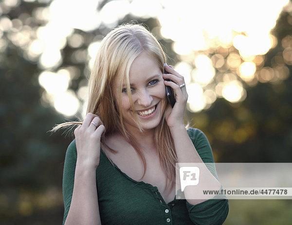 Frauen lächeln mit dem Handy in der Natur