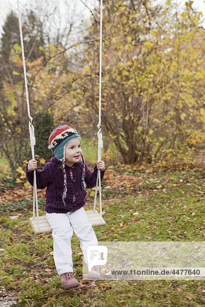 Kleines Mädchen auf einer Schaukel im Garten