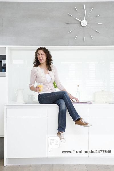 Frau auf Kochnische sitzend