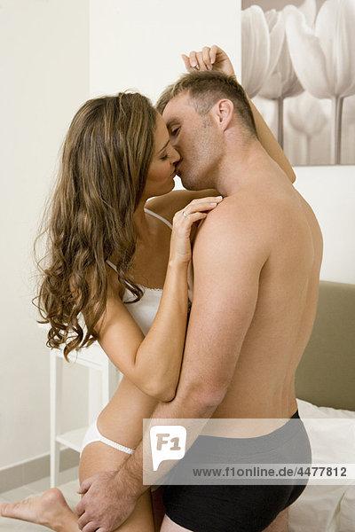 Junges halbnacktes Paar  das sich auf dem Bett küsst.