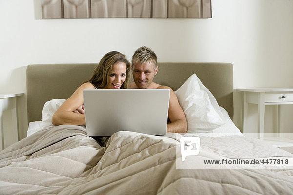 Junges Paar mit Laptop im Bett