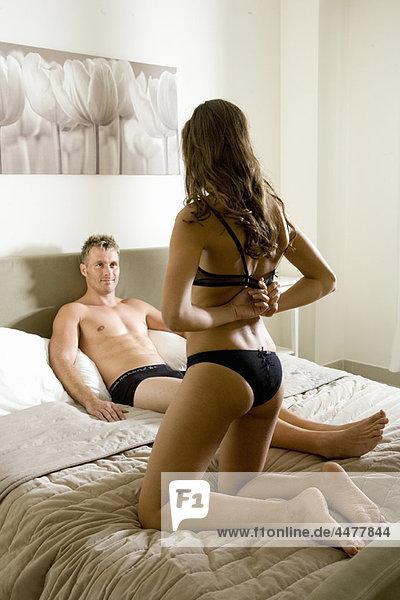 Junge Frau beim Strippen für Mann im Bett
