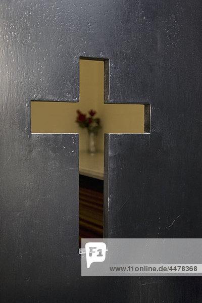 Detail eines Kreuzausschnittes in der Tür einer Kirche