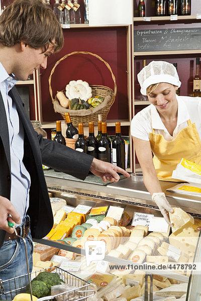 Ein Kunde und Angestellter in einem Wein- und Käseladen