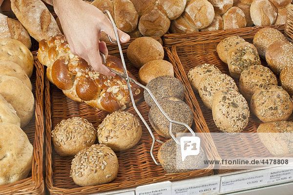 Ein Verkäufer  der eine Rolle mit einer Zange in einer Bäckerei abholt  konzentriert sich auf die Hand.