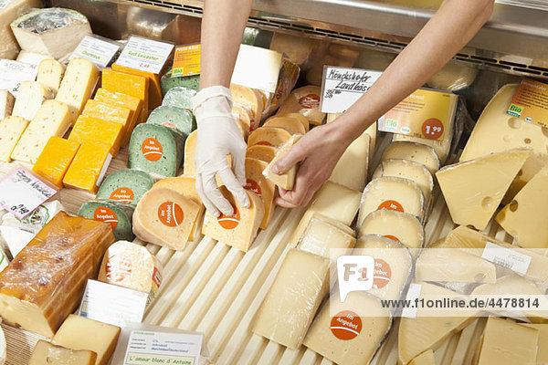 Eine Verkäuferin in einem Käseladen  die sich auf die Hände konzentriert.