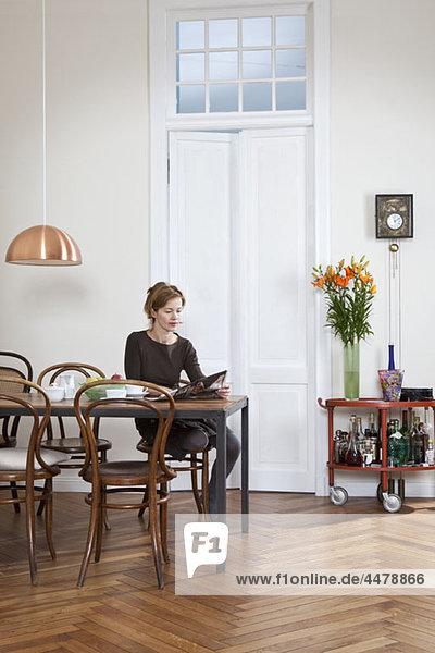 Eine Frau  die Kaffee trinkt und die Zeitung liest.