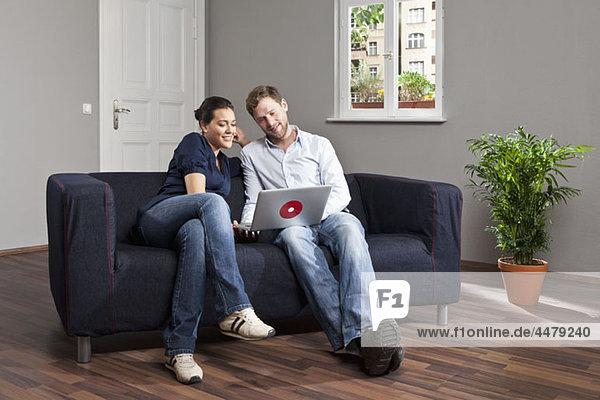 Ein junges Paar mit einem Laptop im Wohnzimmer