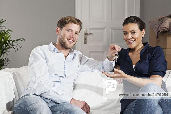 Ein Mann  der einer Frau einen Schlüssel für ihr neues Haus gibt.