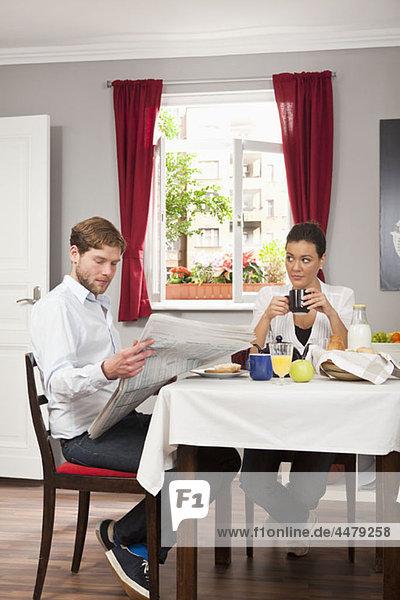 Eine Frau sieht irritiert aus  während ihr Freund sie am Frühstückstisch ignoriert.