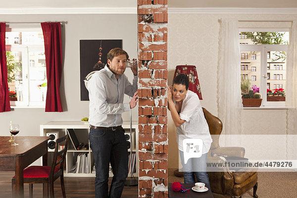 Mann und Frau lauschen auf beiden Seiten der Wand mit Trinkgläsern