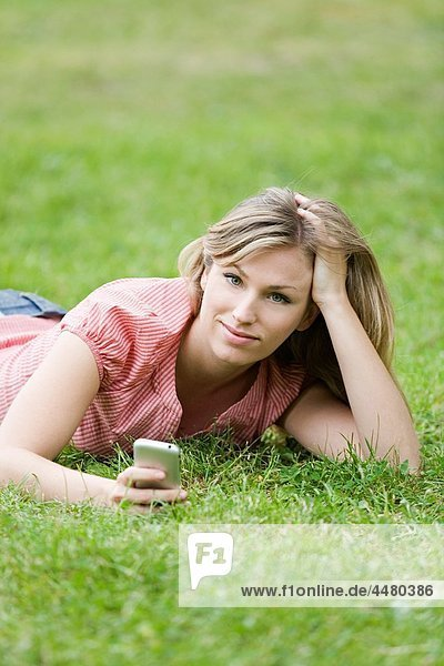 Blonde woman lying down on the grass with mobile