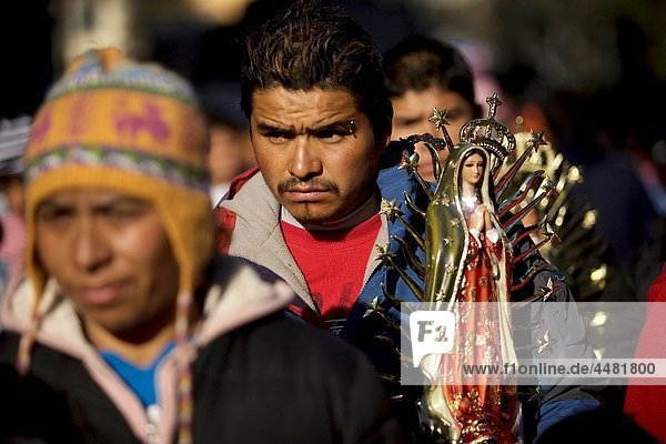 A pilgrim carries a statue of the Our Lady of Guadalupe outside the Our Lady of Guadalupe Basilica in Mexico City  December 11  2010 Hundreds of thousands of Mexican pilgrims converged on the Basilica  bringing images to be blessed  as processions filled