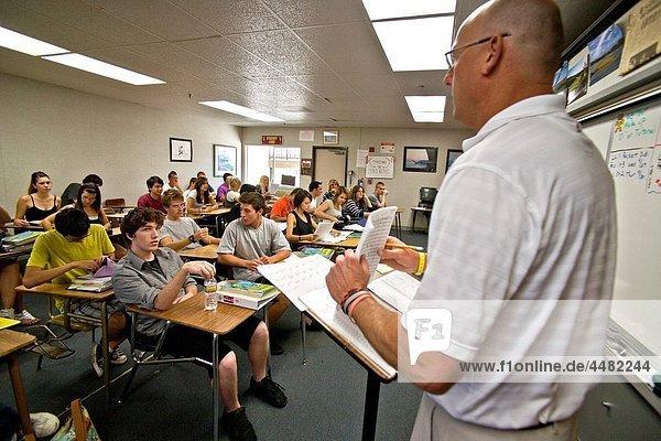 Using a check list  a Southern California high school teacher checks attendance at the beginning of a class period