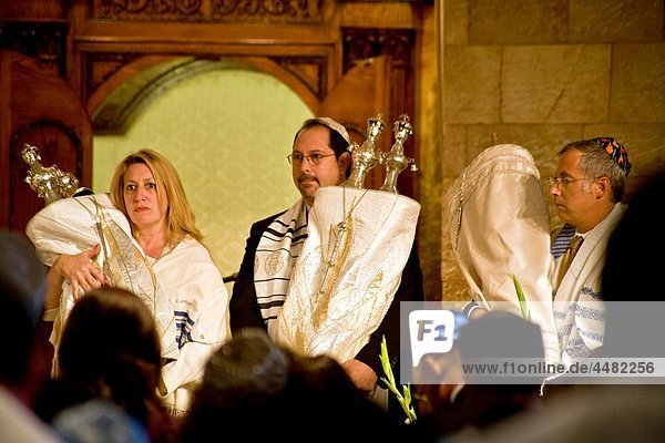 Wearing ceremonial white  a rabbi and congregation members hold Torah scrolls at Yom Kippur service at a California reform synagogue Known as the ´Day of Atonement ´ Yom Kippur is one of holiest days of the year for Jewish people Note woman participatin