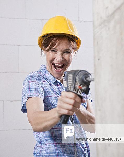 Lachende Frau mit Schutzhelm und Bohrmaschine
