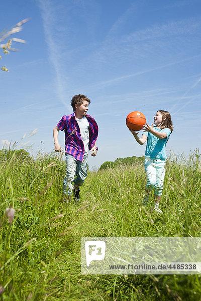 Zwei Kinder laufen mit Ball über eine Wiese