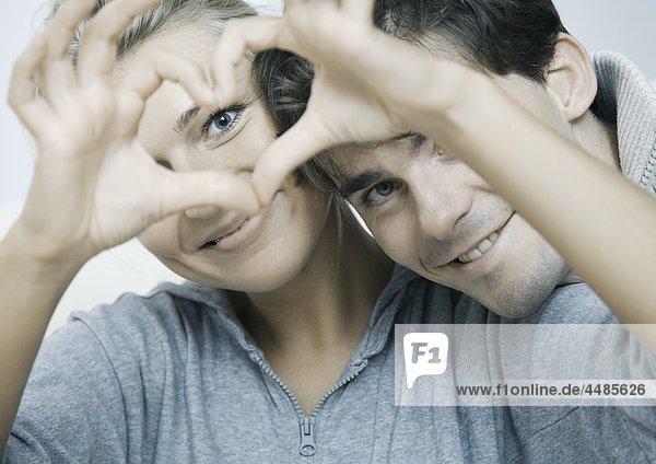 Verliebtes junges Paar formt ein Herz mit ihren Händen