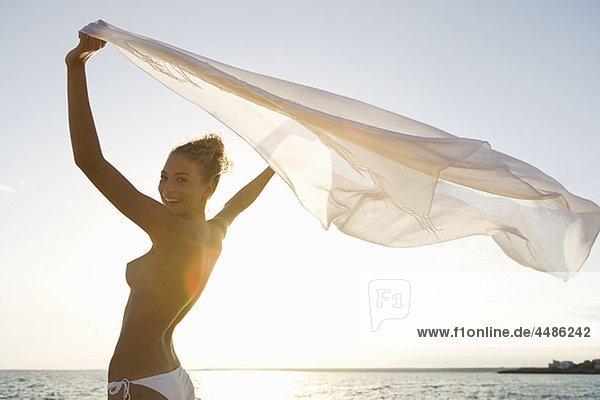 Lächelnde Frau oben ohne mit Tuch am Strand pe0075162