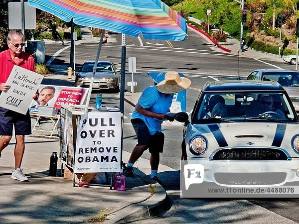 An activist seeking the impeachment of US President Barack Obama distributes handbills to passing drivers outside a post office in Laguna Niguel  CA while a counter demonstrator at left carries a sign denouncing the activist´s organization
