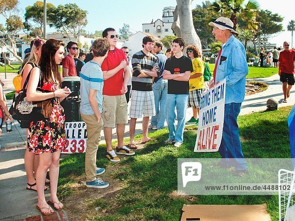 An antiwar activist protesting the Afghanistan war talks with teenage well-wishers at an outdoor demonstration in Laguna Beach  California